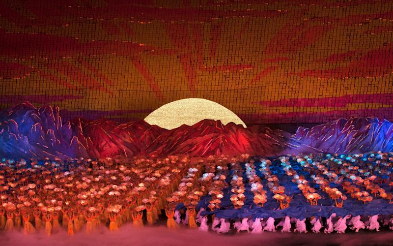 North Korean dancers in front of rising sun over mount Paektu made by children holding up boards during Arirang mass games - Corbis News