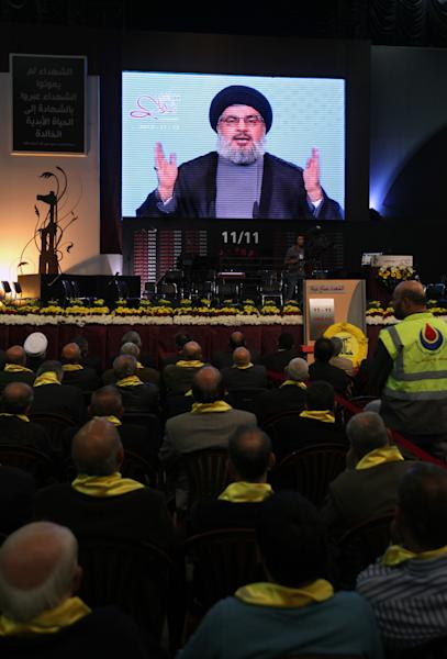 In this photo taken on Monday, Nov. 12, 2012, Hezbollah leader Sheik Hassan Nasrallah, speaks via a video link during a rally to mark the Hezbollah martyr day, in the southern suburb of Beirut, Lebanon. With the death toll from the Israel-Gaza conflict mounting, Hezbollah has offered quiet words of encouragement to the Palestinians, pledging support and calling on Arab states to send them weapons to fight Israel. But beyond that, the Lebanese militant group appears to be staying firmly on the sidelines. (AP Photo/Bilal Hussein)