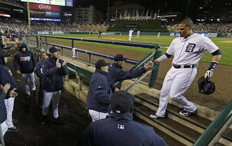 Detroit Tigers' Victor Martinez is greeted as he walks into the dugout after scoring in the sixth inning during Game 5 of the American League baseball championship series against the Boston Red Sox, Thursday, Oct. 17, 2013, in Detroit. (AP Photo/Matt Slocum)