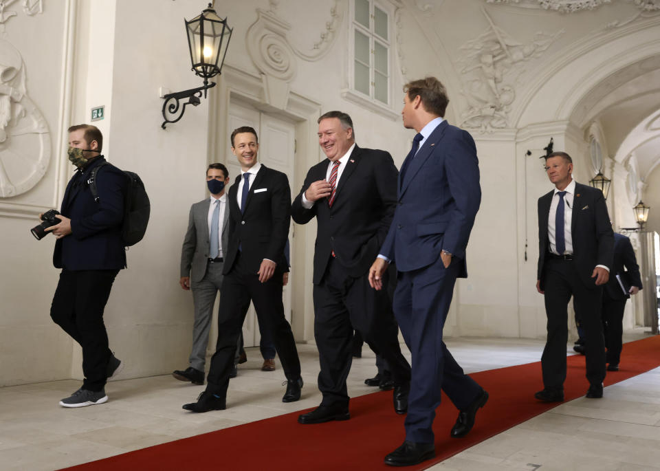 U.S. Secretary of State Mike Pompeo, center, Austrian Finance Minister Gernot Bluemel, second left, and U.S. ambassador to Austria Trevor Traina, second right, arrive for a business roundtable at the Winter Palace in Vienna Austria, Friday Aug. 14, 2020. Pompeo is on a five-day visit to central Europe. (Lisi Niesner/Pool via AP)