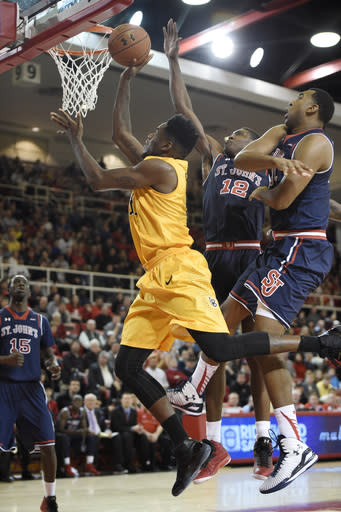 Long Beach State's forward David Samuels (11) drives the ball to the basket past St. John's forward Chris Obekpa (12) and center Joey De La Rosa (34) during the first half of an NCAA college basketball game Monday, Dec. 22, 2014 in New York. (AP Photo/Kathy Kmonicek)
