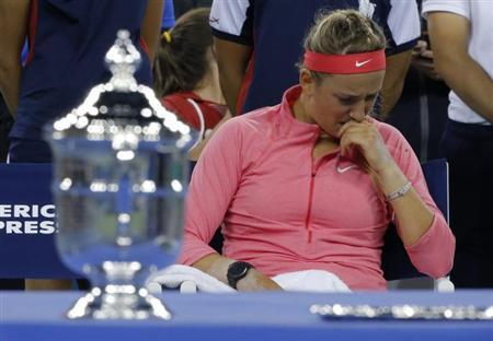Victoria Azarenka of Belarus wipes her face as she sits by the winner's trophy (L) after being defeated by Serena Williams of the U.S. in their women's singles final match at the U.S. Open tennis championships in New York September 8, 2013. REUTERS/Eduardo Munoz