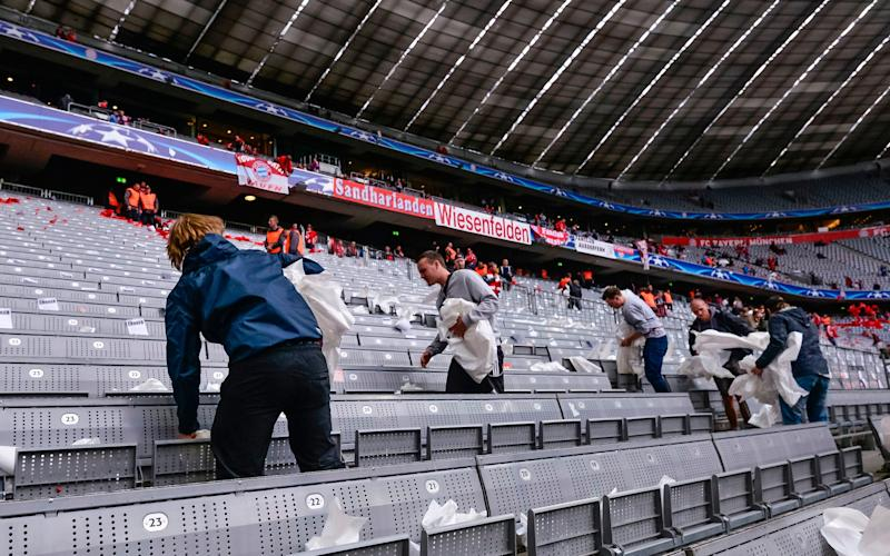 volunteers have to remove paper from bayern munich stadium - Credit: AFP
