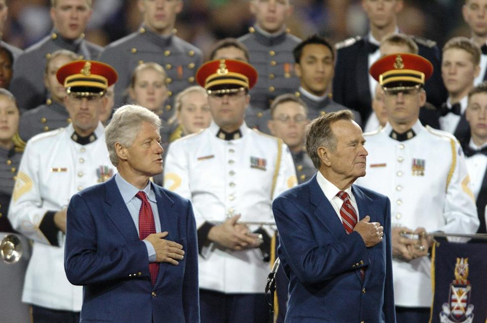 Former US presidents George H.W. Bush (R) and Bill Clinton listen to the national anthem sung by the combined choirs of the U.S. Military Academythe U.S. Naval Academy, the U.S. Air Force Academy, and the U.S. Coast Guard Academy, and the U.S. Army Herald Trumpetsbefore the start of Super Bowl XXXIX between the Philadelphia Eagles and the New England Patriots on Feb. 6, 2005at Alltel Stadium in Jacksonville, Florida.