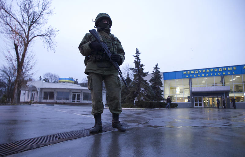An unidentified armed man patrols a square in front of the airport in Simferopol, Ukraine, on Friday, Feb. 28, 2014. Dozens of armed men in military uniforms without markings occupied the airport in the capital of Ukraine's strategic Crimea region early Friday. (AP Photo/Ivan Sekretarev)