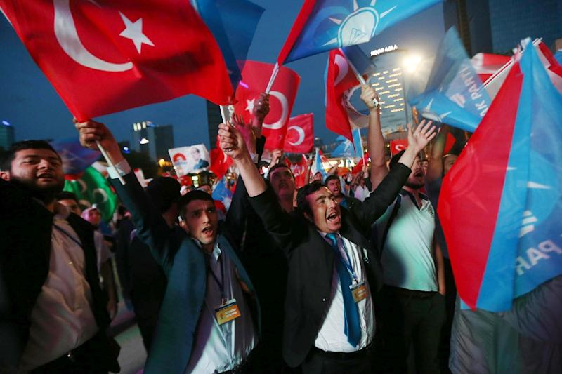 Supporters of Turkey's Islamic-rooted Justice and Development Party (AKP) wave Turkish flags as they celebrate the results of the legislative election outside AKP's headquarters in Ankara on June 7, 2015 (AFP Photo/Adem Altan)