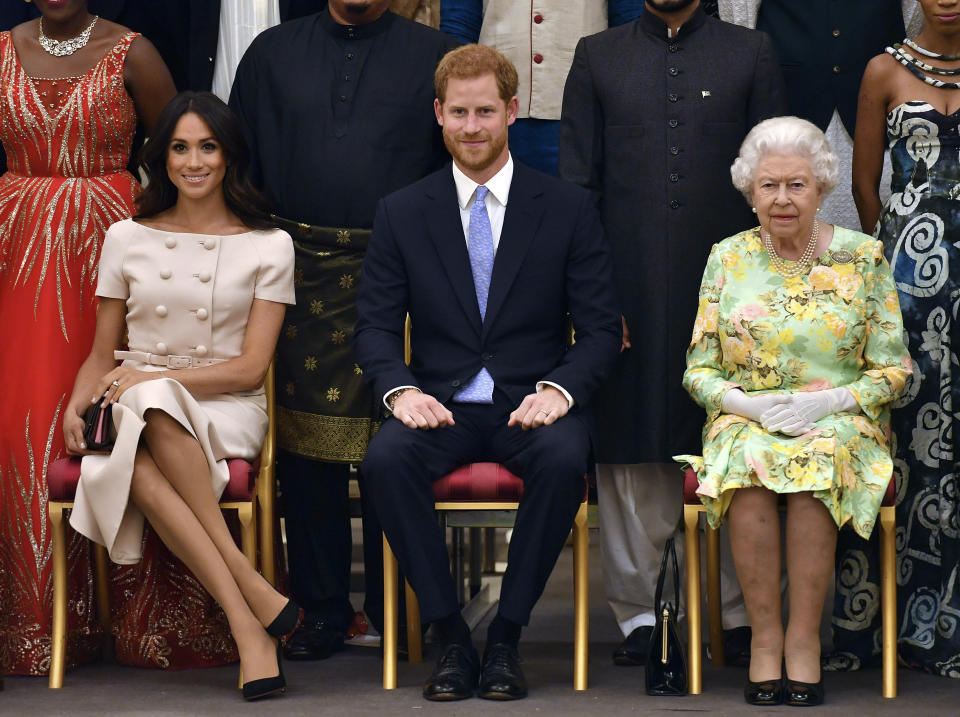 """FILE - In this Tuesday, June 26, 2018 file photo Britain's Queen Elizabeth, Prince Harry and Meghan, Duchess of Sussex pose for a group photo at the Queen's Young Leaders Awards Ceremony at Buckingham Palace in London. In a stunning declaration, Britain's Prince Harry and his wife, Meghan, said they are planning """"to step back"""" as senior members of the royal family and """"work to become financially independent."""" A statement issued by the couple Wednesday, Jan. 8, 2020 also said they intend to """"balance"""" their time between the U.K. and North America. (John Stillwell/Pool Photo via AP, File)"""