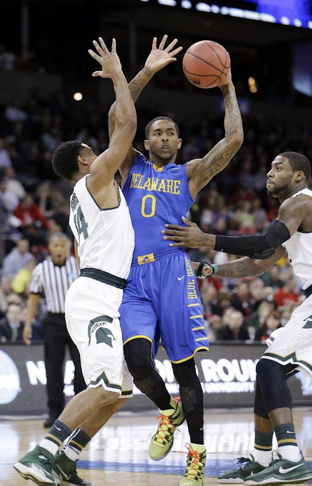 Delaware's Davon Usher (0) looks for room to pass as Michigan State's Gary Harris, left, and Branden Dawson defend in the first half during the second round of the NCAA college basketball tournament in Spokane, Wash., Thursday, March 20, 2014. (AP Photo/Elaine Thompson)