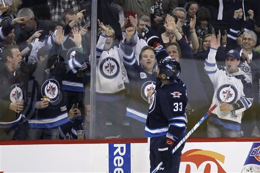 Winnipeg Jets' Dustin Byfuglien (33) salutes his fans after scoring against the Florida Panthers during the second period of their NHL hockey game in Winnipeg, Manitoba, Thursday, April 11, 2013. (AP Photo/The Canadian Press, John Woods)