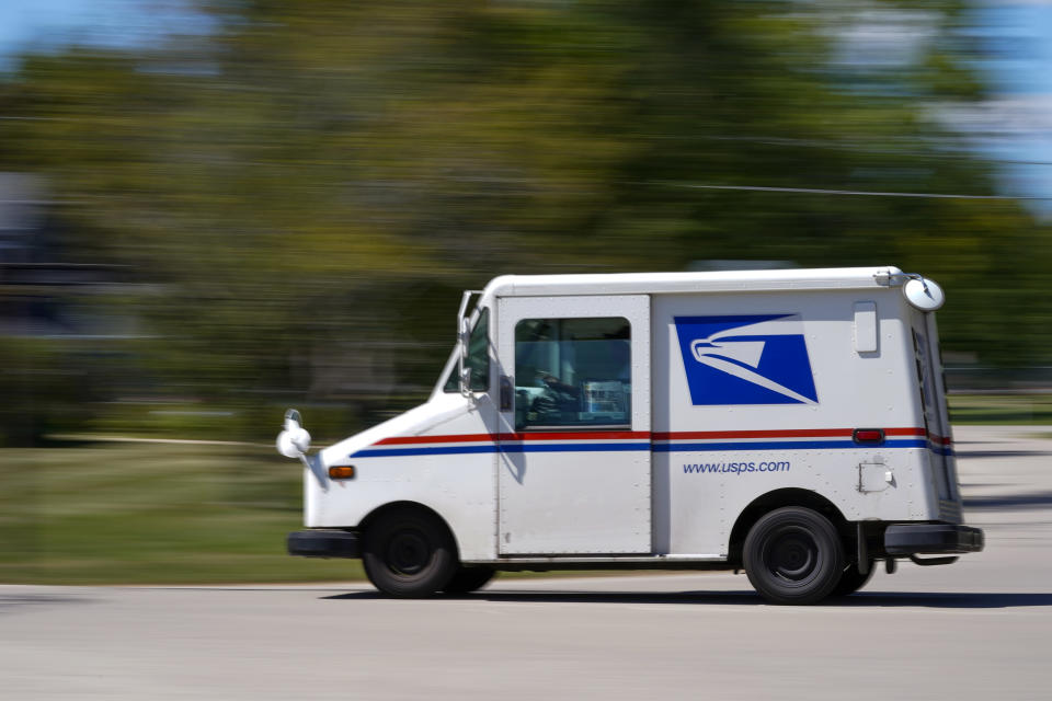 A mail truck moves down a street Tuesday, Aug. 18, 2020, in Fox Point, Wis. Facing public pressure and state lawsuits, the Postmaster general announced Tuesday he is halting some operational changes to mail delivery that critics warned were causing widespread delays and could disrupt voting in the November election. (AP Photo/Morry Gash)