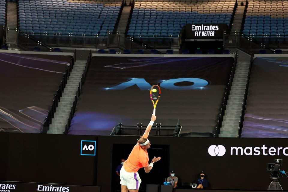 Empty seats are pictured in the background as Spain's Rafael Nadal serves against Greece's Stefanos Tsitsipas during their men's singles quarter-final match on day ten of the Australian Open tennis tournament in Melbourne on February 17, 2021. (Photo by DAVID GRAY / AFP) / -- IMAGE RESTRICTED TO EDITORIAL USE - STRICTLY NO COMMERCIAL USE -- (Photo by DAVID GRAY/AFP via Getty Images)