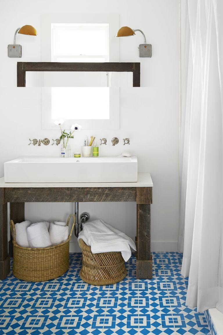 <p>Patterned blue-and-white tile floors steal the show in this bathroom design scheme. </p>