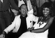 <p>Tina Turner sits next to fashion photographer Francesco Scavullo at New York's famous Studio 54 nightclub in 1977. The Queen of Rock and Roll was dressed in typical '70s style, wearing a loose strapless dress and statement necklace. </p>