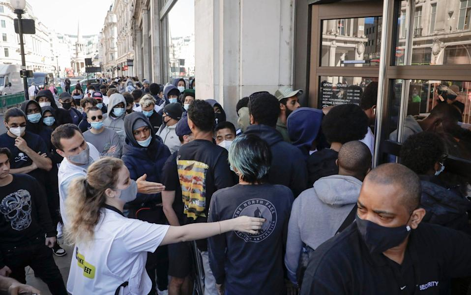 Shoppers crowd to get into the Niketown store on Oxford Street - Matt Dunham/AP