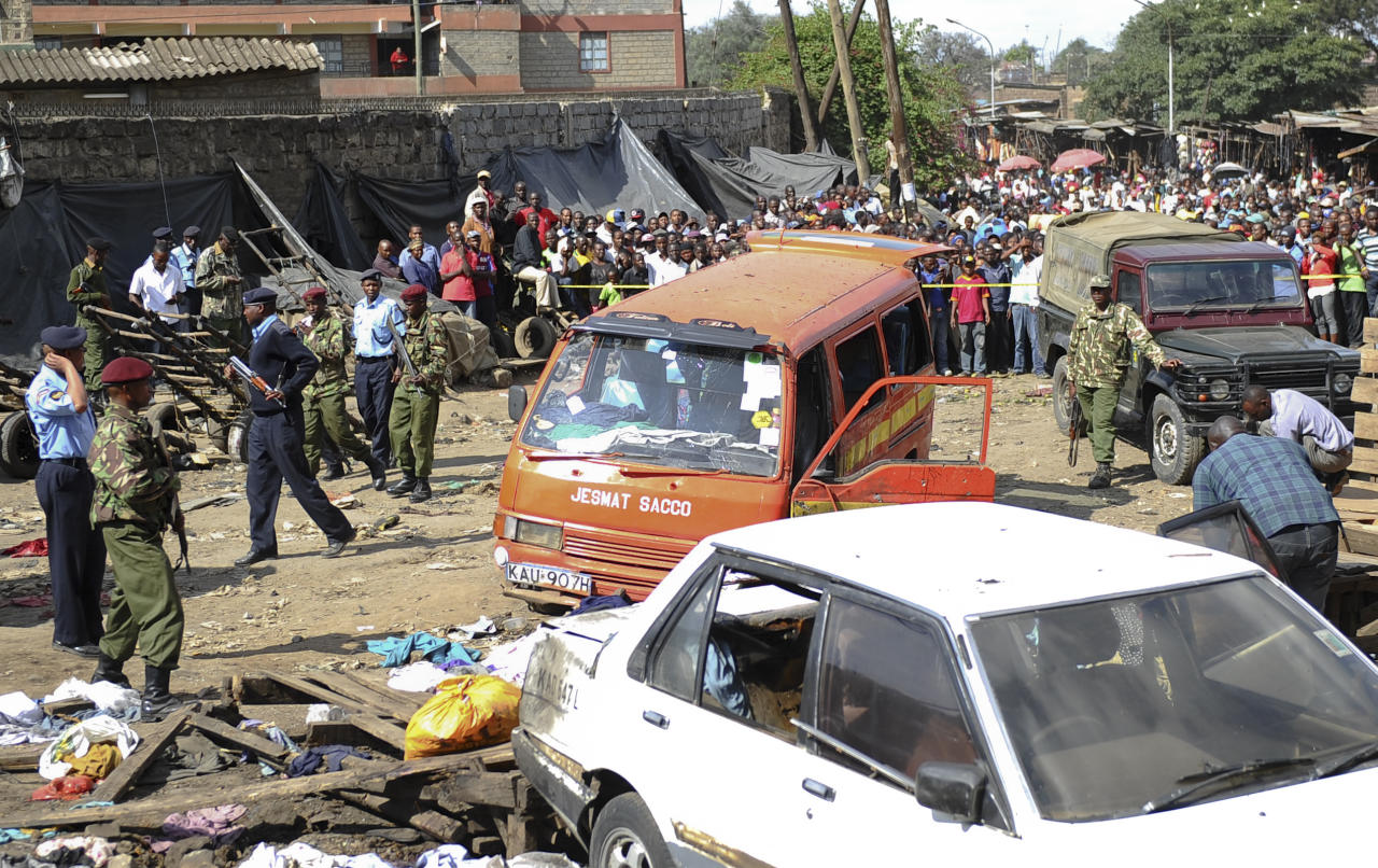 EDS NOTE: RECROP OF NAI113. Security forces secure the scene at the site where two blasts detonated, one in a mini-van used for public transportation, in a market area of Nairobi, Kenya Friday, May 16, 2014. Two blasts hit Kenya's capital on Friday, killing a number of people and injuring many more, in what appeared to be the latest in a string of increasingly frequent terror attacks. (AP Photo)