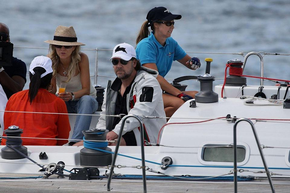 """<p>Russell Crowe is on a boat with Oprah (with her back to us in the orange shirt) and still looks like """"meh, this is fine."""" </p>"""