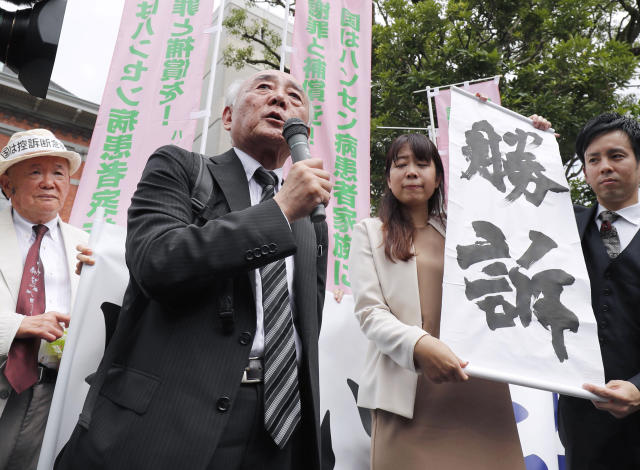 "FILE - In this June 28, 2019, file photo, lawyer Yasuyuki Tokuda, second from left, speaks after Kumamoto District Court ordered compensation for kin of leprosy patients, in Kumamoto, southern Japan. Japanese Prime Minister Shinzo Abe said Tuesday, July 9, 2019 it will not challenge the recent court ruling awarding damages to former leprosy patients' families for their suffering from discrimination caused by the government's failure to end its isolation policy. The sign at right reads: ""Winning lawsuit."" (Kyodo News via AP)"