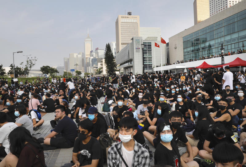 Students and others gather during a demonstration at Edinburgh Place in Hong Kong, Thursday, Aug. 22, 2019. High school students thronged a square in downtown Hong Kong Thursday to debate political reforms as residents gird for further anti-government protests. (AP Photo/Vincent Yu)