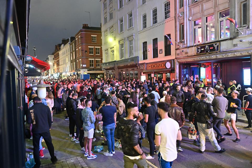 Revellers crowd the street outside bars in the Soho area of London on July 4, 2020, as restrictions are further eased during the novel coronavirus COVID-19 pandemic. - Pubs in England reopen on Saturday for the first time since late March, bringing cheer to drinkers and the industry but fears of public disorder and fresh coronavirus cases. (Photo by JUSTIN TALLIS / AFP) (Photo by JUSTIN TALLIS/AFP via Getty Images)