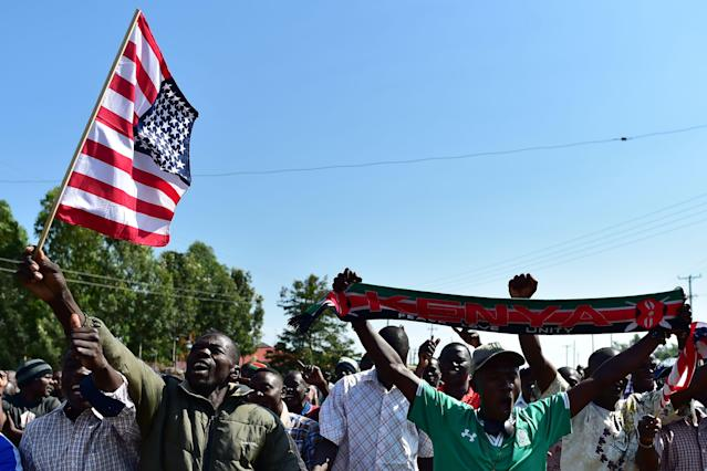 <p>Residents of Nyang'oma village in Kogelo wave US flags as they gather by the side of the road to wait for former US President, Barak Obama to arrive on July 16, 2018 for the opening of the Sauti Kuu Resource Centre, founded by his half-sister, Auma Obama at Kogelo in Siaya county, western Kenya. – Obama is in the East African nation for the first time since he left the US presidency and met with President Uhuru Kenyatta and opposition leader Raila Odinga in Nairobi. (Photo: Tony Karumba/AFP/Getty Images) </p>