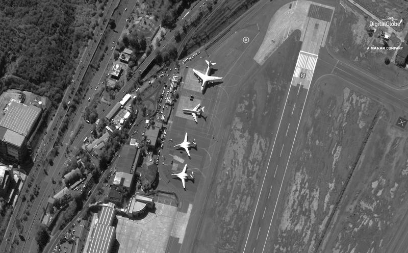 FILE - In this Dec. 10, 2018 file satellite image provided by DigitalGlobe shows the Simon Bolivar International Airport shortly after four Russian military aircraft arrived in Maiquetia, Venezuela. What the U.S. considers Russia's destabilizing support for Venezuelan President Nicolas Maduro hit a high point in December when two Russian bombers capable of carrying nuclear weapons, bottom of photo, touched down in Caracas. (DigitalGlobe, a Maxar company via AP, File)