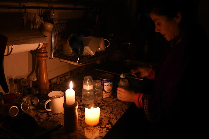 A woman prepares milk bottles by candle lights at her home in Montevideo during a massive power failure (AFP Photo/MIGUEL ROJO)