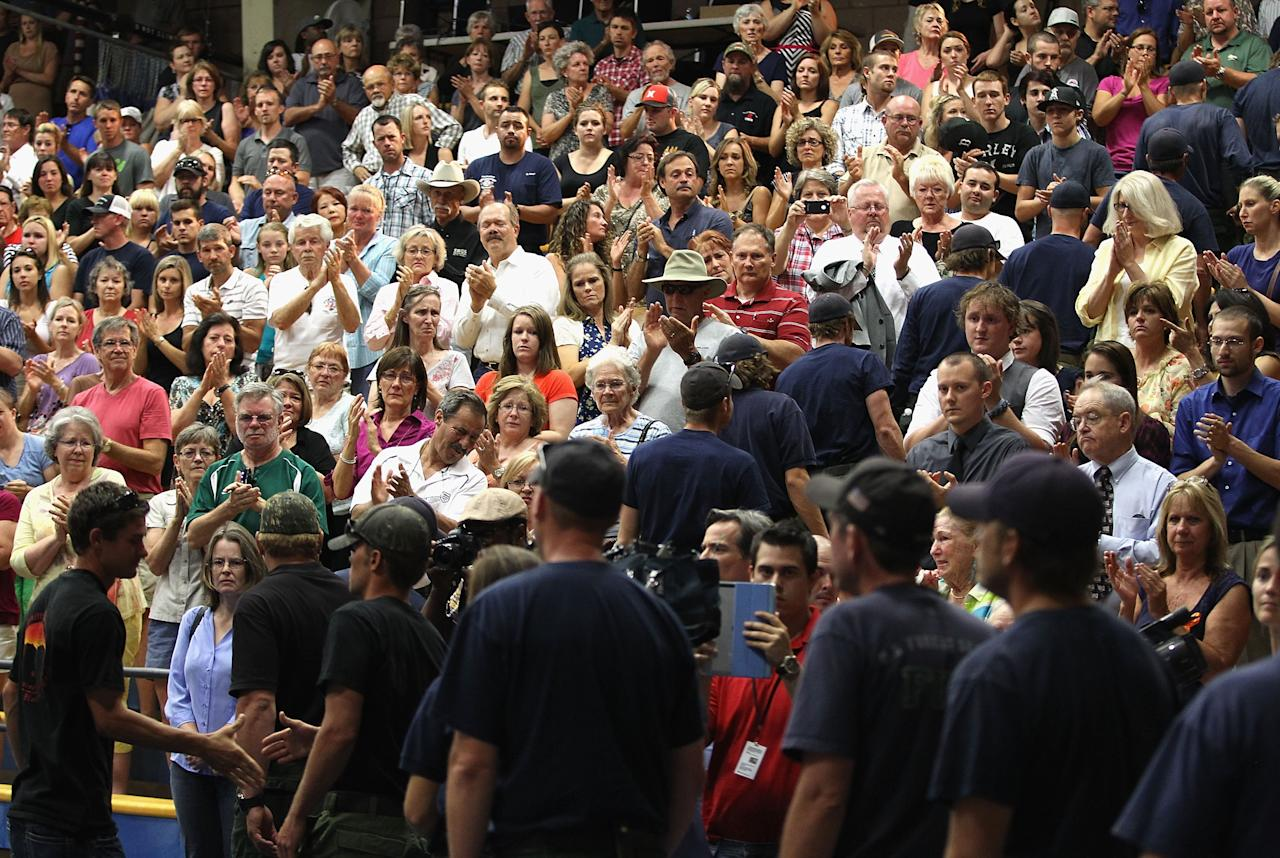 PRESCOTT, AZ - JULY 01: Firefighters recieve a standing ovation as they arrive to the memorial service at EmbryRiddle Aeronautical University on July 1, 2013 in Prescott, Arizona. On Sunday 19 Granite Mountain Interagency Hotshot Crew firefighters died battling a fast-moving wildfire near Yarnell, AZ. (Photo by Christian Petersen/Getty Images)