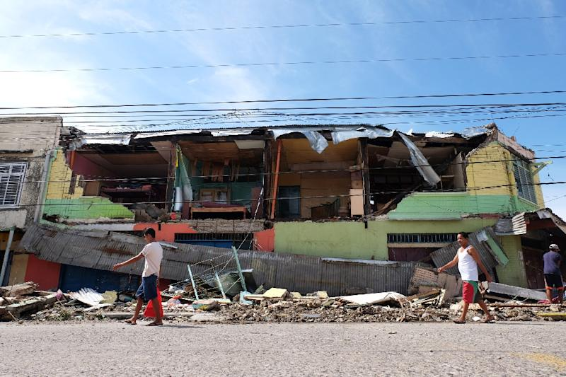 Residents walk past a house destroyed by Typhoon Melor after it hit Bulan town in Sorsogon province on December 15, 2015 (AFP Photo/Charism Sayat)