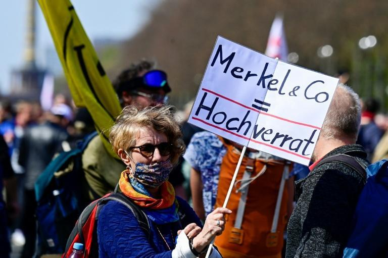 """A protester holds a placard accusing Merkel of """"high treason"""""""