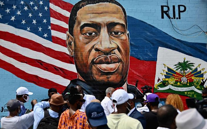 People gather at the unveiling of artist Kenny Altidor's memorial portrait of George Floyd - Angela Weiss/AFP