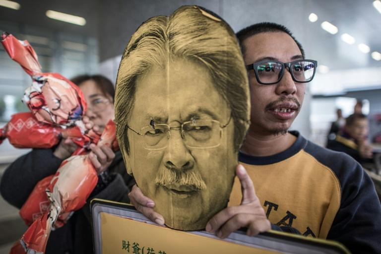 A demonstrator holds a placard depicting Hong Kong's Financial Secretary John Tsang Chun-wah, as people protest against the new budget, outside the government buildings, on February 24, 2016