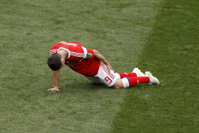 Russia's Alan Dzagoev reacts as he holds his leg during the group A match between Russia and Saudi Arabia which opens the 2018 soccer World Cup at the Luzhniki stadium in Moscow, Russia, Thursday, June 14, 2018. (AP Photo/Darko Bandic)