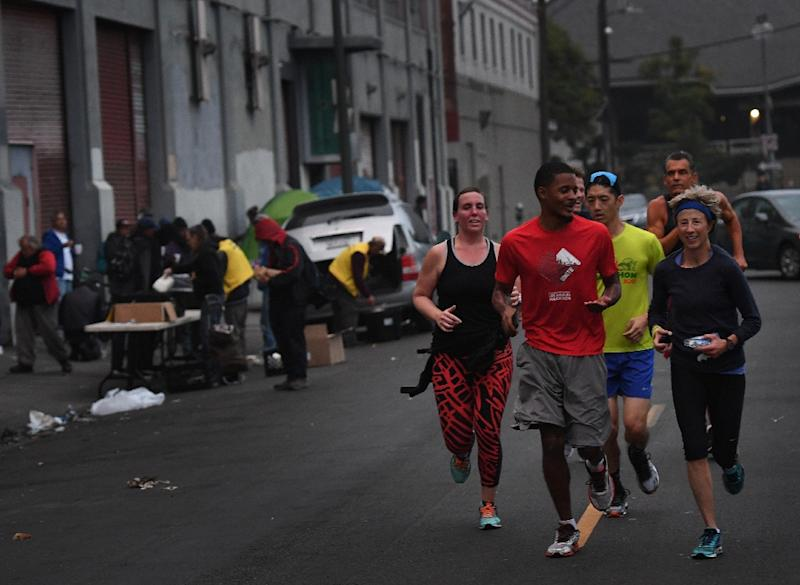 Members of the Midnight Runners team, which is made up mostly of recovering addicts and homeless people, run through the streets of Skid Row in Los Angeles (AFP Photo/Mark RALSTON)