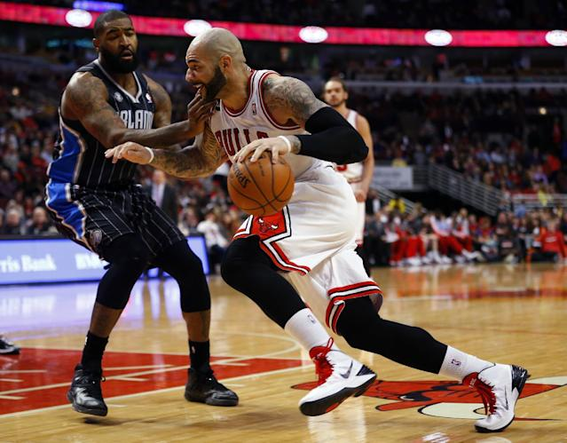 Chicago Bulls forward Carlos Boozer, right, dribbles past Orlando Magic forward Kyle O'Quinn, left, during the second half of an NBA basketball game Monday, April 14, 2014, in Chicago. The Bulls won the game 108-95. (AP Photo/Jeff Haynes)