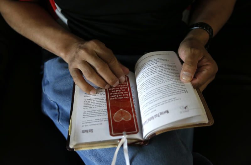In this photo taken April 20, 2017, Joseph Rodriguez looks over his devotional book in his sister's home in Chicago. The 51-year-old Chicagoan spent 35 years in prison for killing two people in a shooting when he was a teenager. A new poll says nearly 7 in 10 older Americans who spent time in prison are anxious about the amount they have saved for retirement. The survey says they are less likely to have income from Social Security, retirement accounts or a pension and more likely to rely on disability payments. More than half worry that the money they do have for retirement won't last over their lifetime. (AP Photo/Charles Rex Arbogast)
