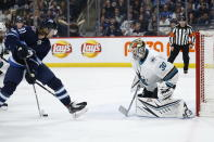 Winnipeg Jets' Kyle Connor (81) takes the shot from between his legs and scores on San Jose Sharks goaltender Aaron Dell (30) during the second period of an NHL hockey game Friday, Feb. 14, 2020, in Winnipeg, Manitoba. (John Woods/The Canadian Press via AP)