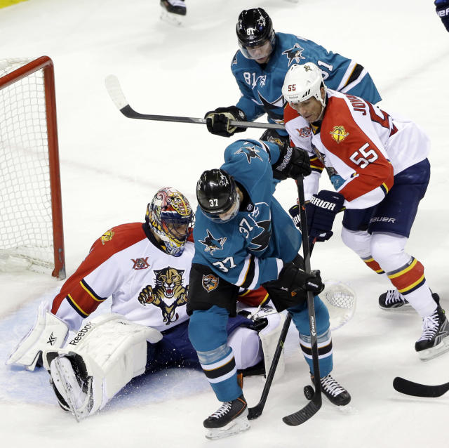 Florida Panthers goalie Roberto Luongo, bottom left, blocks a shot attempt from San Jose Sharks' Adam Burish (37) during the second period of an NHL hockey game on Tuesday, March 18, 2014, in San Jose, Calif. (AP Photo/Marcio Jose Sanchez)
