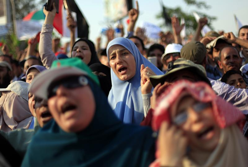 """Supporters of Egypt's president Mohammed Morsi chant slogans during a rally in Nasser City in Cairo, Egypt, Friday, June 21, 2013. Tens of thousands of Islamists supporting Egypt's president staged a show of force ahead of massive protests later this month by the opposition, chanting """"Islamic revolution"""" and warning of a new and bloody bout of turmoil. Adding to the combustible mix, the U.S. ambassador in Egypt gets drawn into Egypt's treacherous politics when comments interpreted as critical of the opposition spark outrage, with one activist telling the diplomat to """"shut up and mind your own business.""""(AP Photo/Khalil Hamra)"""