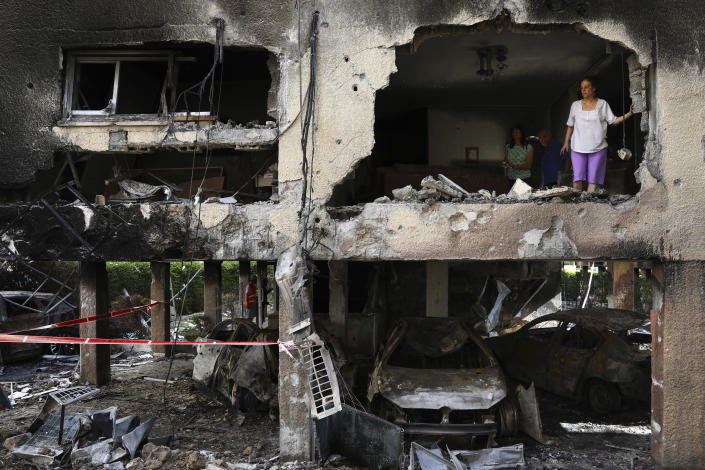 Members of Sror family inspect the damage of their apartment after it was hit by a rocket fired from the Gaza Strip over night in Petah Tikva, central Israel, Thursday, May 13, 2021. (AP Photo/Oded Balilty)