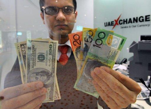 A money changer displays a selection of US dollars (L) and Australian polymer notes (R) in Sydney on May 14, 2012. The Australian dollar dropped below parity with the greenback on Monday for the first time since December as political turmoil in Greece led traders to sell riskier assets