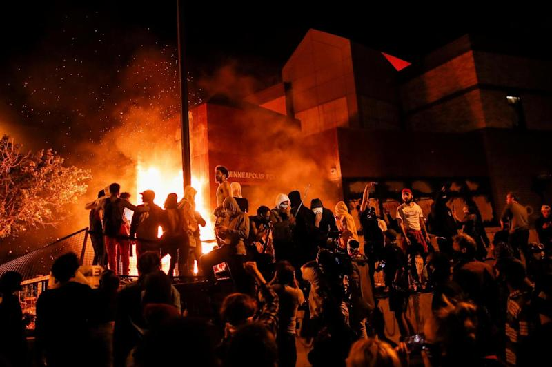 Protesters gather around after setting fire to the entrance of a police station as demonstrations continue: Reuters