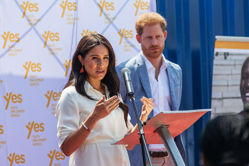 """Meghan, Duchess of Sussex(L), is watched by Britain's Prince Harry, Duke of Sussex(R) as she delivers a speech at the Youth Employment Services Hub in Tembisa township, Johannesburg, on October 2, 2019. - Meghan Markle is suing Britain's Mail On Sunday newspaper over the publication of a private letter, her husband Prince Harry has said, warning they had been forced to take action against """"relentless propaganda""""."""