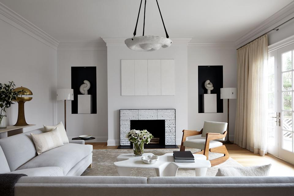 "<div class=""caption""> The monochromatic living room is a study in textural contrasts thanks to a fiberglass resin cocktail table by Paul Mathieu, a custom rocking chair by <a href=""https://carltonhouse.net/stockists"" rel=""nofollow noopener"" target=""_blank"" data-ylk=""slk:Carlton House Restoration"" class=""link rapid-noclick-resp"">Carlton House Restoration</a> covered in <a href=""http://www.nacarat.be/"" rel=""nofollow noopener"" target=""_blank"" data-ylk=""slk:Charles Schambourg"" class=""link rapid-noclick-resp"">Charles Schambourg</a> leather, a plaster pendant by William P. Sullivan from <a href=""http://www.maisongerard.com/"" rel=""nofollow noopener"" target=""_blank"" data-ylk=""slk:Maison Gerard"" class=""link rapid-noclick-resp"">Maison Gerard</a>, and a ceramic wall sculpture by Peter Lane. </div>"