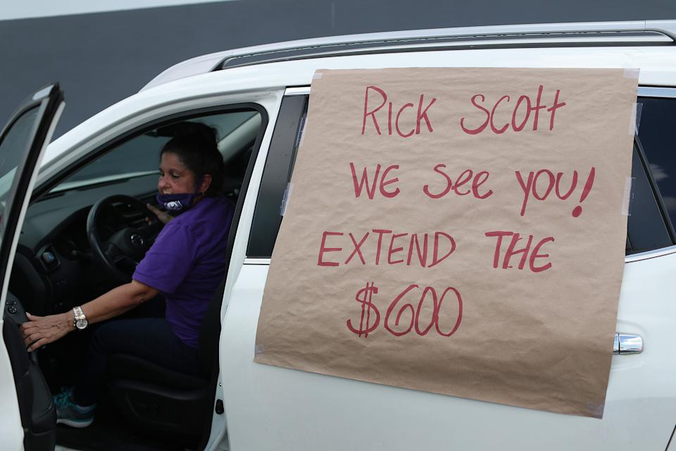 MIAMI SPRINGS, FLORIDA - JULY 16: A car with, 'Rick Scott We See You! Extend the $600!', on it participates in a caravan protest on July 16, 2020 in Miami Springs, Florida.  The caravan was driving to the Coral Gables office of Sen. Rick Scott to ask him and other Senators to support the new Schumer/Wyden legislation that extends unemployment benefits for all laid-off Americans as the coronavirus pandemic continues to disrupt the economy.  (Photo by Joe Raedle/Getty Images)