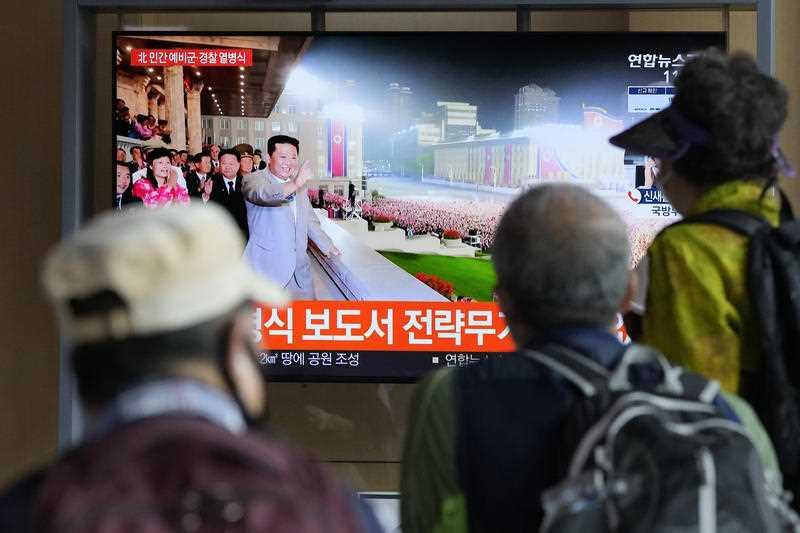 People watch a TV showing North Korean leader Kim Jong Un during a military parade held in Pyongyang, North Korea, at Seoul Railway Station in Seoul, South Korea.