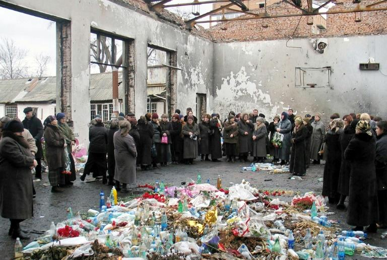 Friends and relatives of victims killed in the 2004 Beslan school hostage massacre gather on March 3, 2005 in the remains of the school in North Ossetia for a minute's silence to commemorate the six-month anniversary of the tragedy
