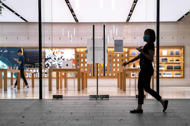 SINGAPORE, SINGAPORE - cA woman wearing a protective mask walk past an empty flagship Apple retail store on Orchard Road on March 15, 2020 in Singapore. The store is temporarily closed after Apple announced that it is closing all stores outside Greater China for 2 weeks due to the coronavirus. (Photo by Ore Huiying/Getty Images)
