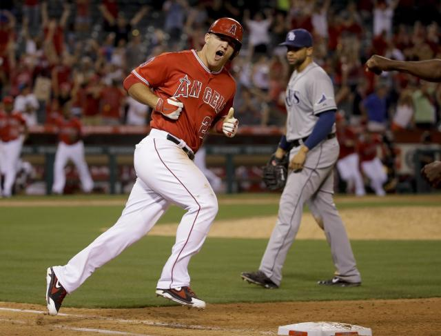 Los Angeles Angels' Mike Trout celebrates his three-run walk off home run as Tampa Bay Rays first baseman James Loney looks on during the ninth inning of a baseball game in Anaheim, Calif., Thursday, May 15, 2014. (AP Photo/Chris Carlson)