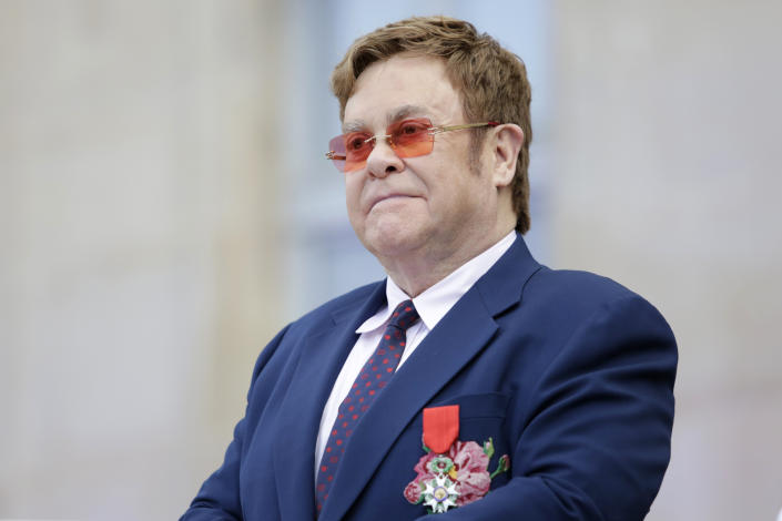 Sir Elton John listens in courtyard of the presidential Elysee Palace in Paris, Friday, June 21, 2019. Sir Elton John received the Legion of Honor, seen on his jacket, France's highest award, during a visit to the presidential Elysee Palace (AP Photo/Lewis Joly, Pool)