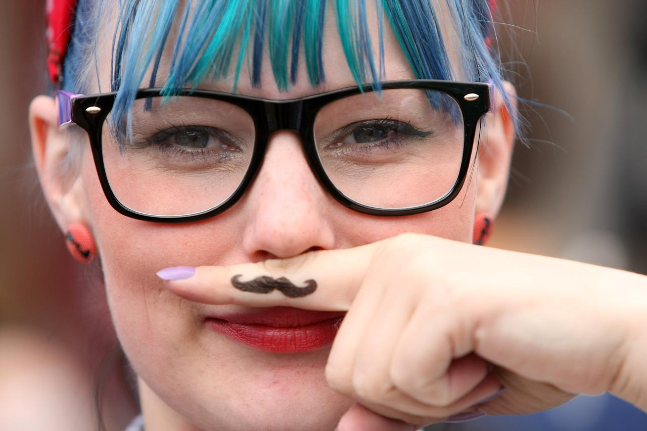 "BERLIN, GERMANY - JULY 21: A visitor uses her finger as an ironic Hipster moustache at the second annual Hipster Olympics on July 21, 2012 in Berlin, Germany. With events such as the ""Horn-Rimmed Glasses Throw,"" ""Skinny Jeans Tug-O-War,"" ""Vinyl Record Spinning Contest"" and ""Cloth Tote Sack Race,"" the Hipster Olympics both mocks and celebrates the Hipster subculture, which some critics claim could never be accurately defined and others that it never existed in the first place. The imprecise nature of determining what makes one a member means that the symptomatic elements of adherants to the group vary in each country, but the archetype of the version in Berlin, one of the more popular locations for those following its lifestyle, along with London and Brooklyn, includes a penchant for canvas tote bags, the carbonated yerba mate drink Club Mate, analogue film cameras, asymetrical haircuts, 80s neon fashion, and, allegedly, a heavy dose of irony. To some in Berlin, members of the hipster ""movement"" have replaced a former unwanted identity in gentrifying neighborhoods, the Yuppie, for targets of criticism, as landlords raise rents in the areas to which they relocate, particularly the up-and-coming neighborhood of Neukoelln.  (Photo by Adam Berry/Getty Images)"
